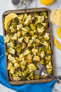 overhead view of roasted broccoli and cauliflower on a baking sheet garnished with lemon