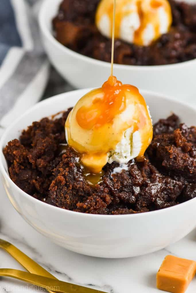 salted caramel crock pot brownies in a white bowl with ice cream and dripping caramel