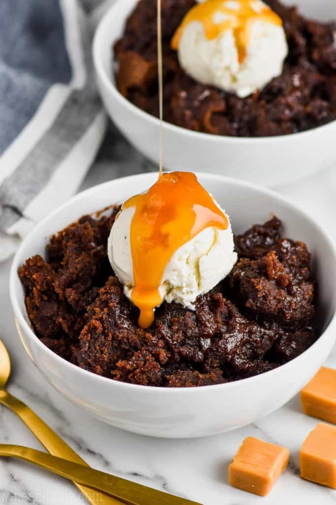dripping caramel sauce over ice cream on a bowl of salted caramel crock pot brownies