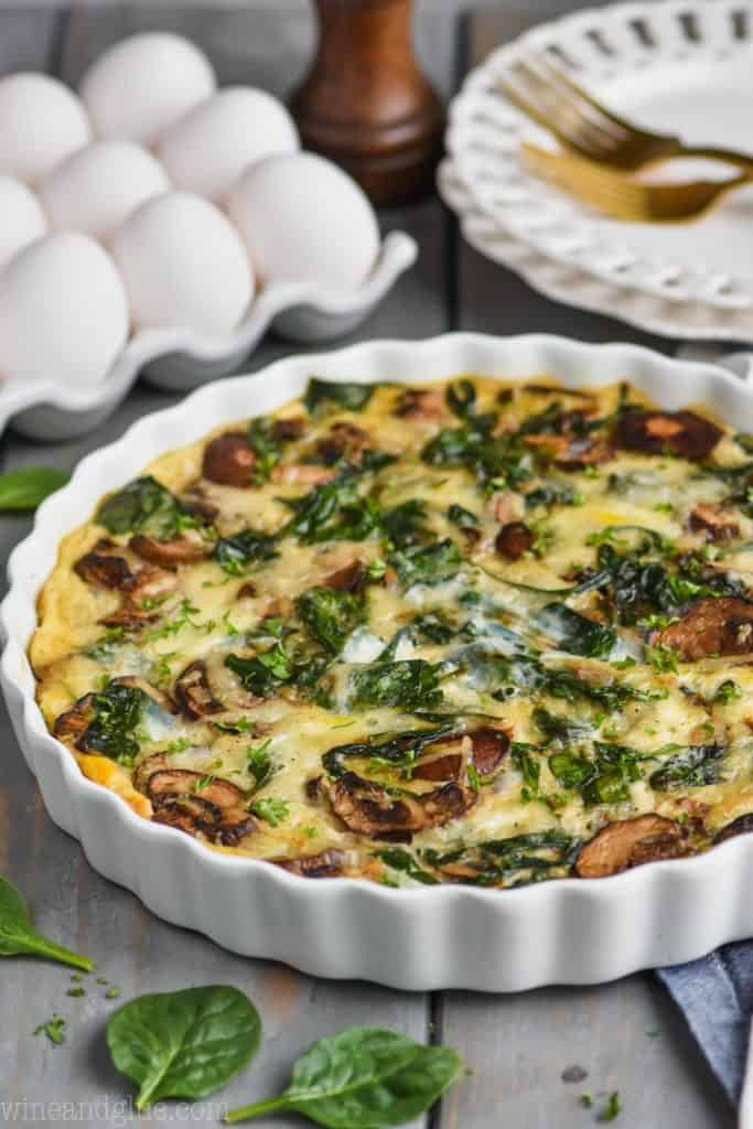a spinach mushroom quiche in a white quiche dish with eggs in the background