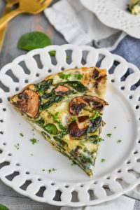 a piece of crustless spinach quiche on a white plate