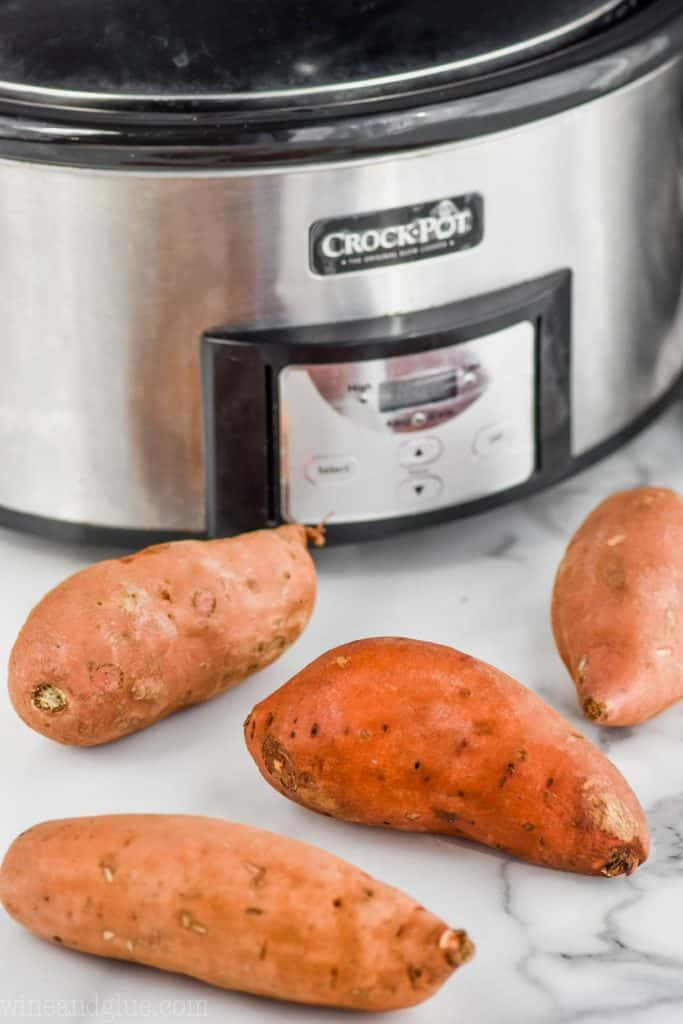four sweet potatoes in front of a slow cooker to show how to cook them in it