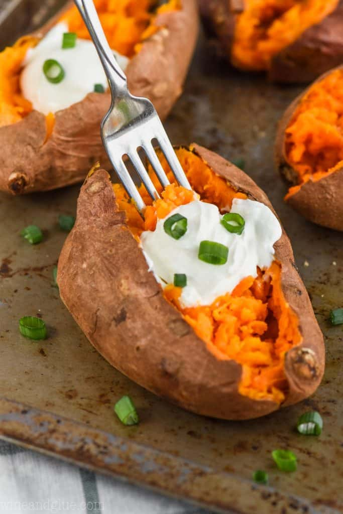 fork digging into a crock pot baked sweet potato with sour cream and green onions