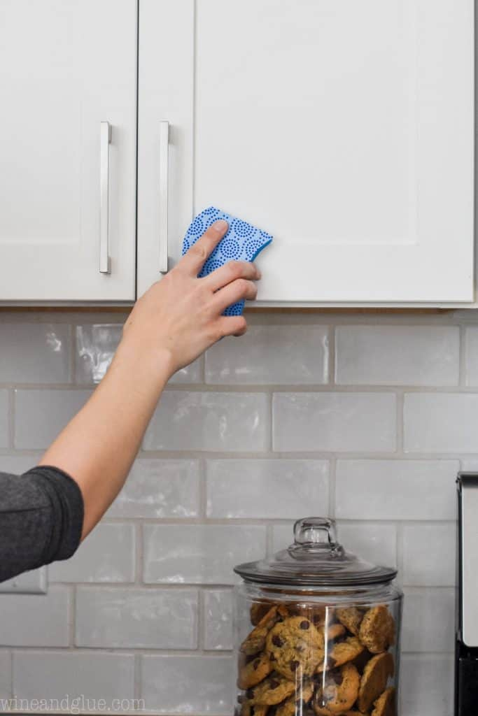 woman using a sponge to clean grease off cabinets