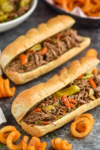 two italian beef sandwiches with curly fries around them on a granite surface