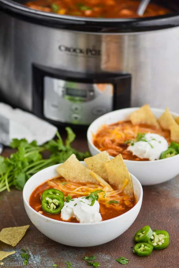 two bowls of easy chicken tortilla soup in front of a crock pot