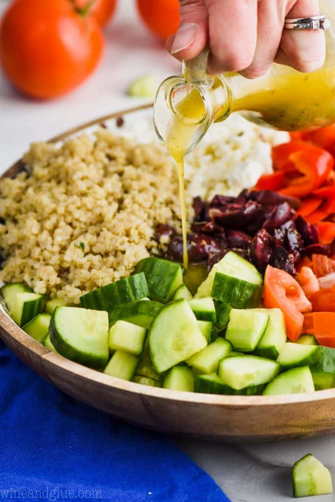 pouring greek salad dressing on greek quinoa salad
