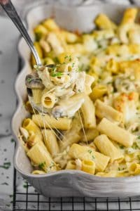 spoon dishing up marsala chicken noodle casserole from a baking dish