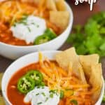 two white bowls filled with slow cooker chicken tortilla soup, garnished with sour cream, shredded cheese, cilantro, jalapeno slices, and tortilla chips