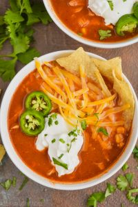 close up overhead view of a bowl of chicken tortilla soup recipe that has been garnished with sour cream, sliced jalapeños, shredded cheese, and tortilla chips