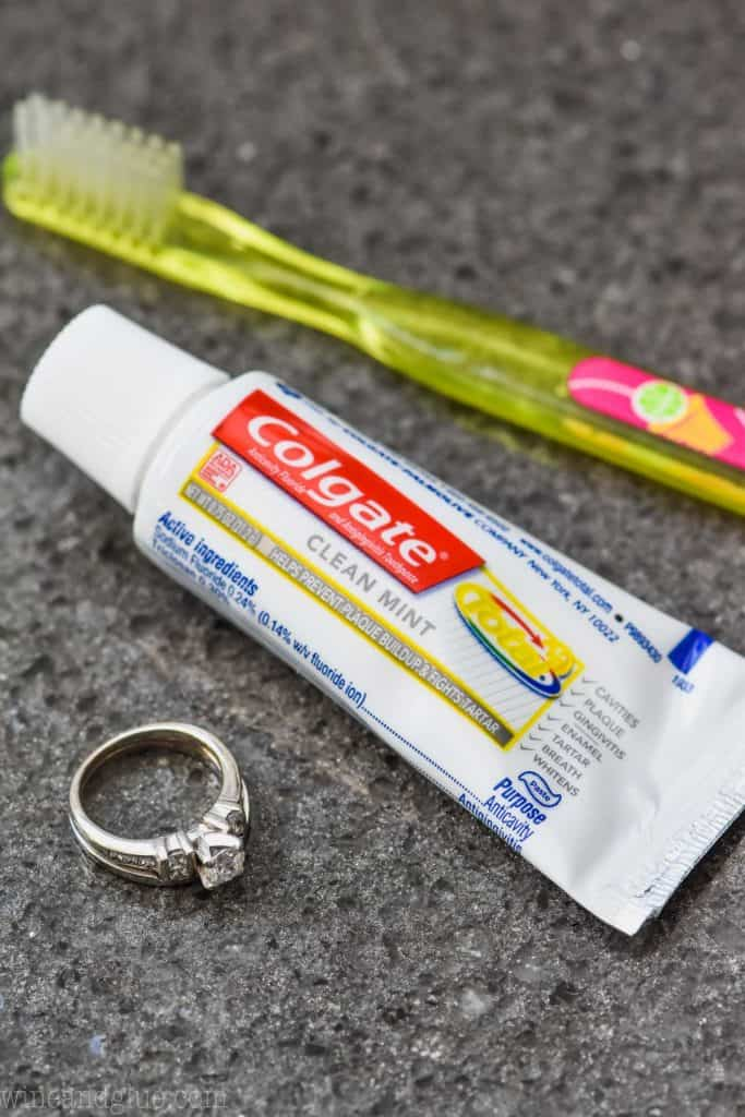 toothpaste and toothbrush on counter with diamond ring to clean it