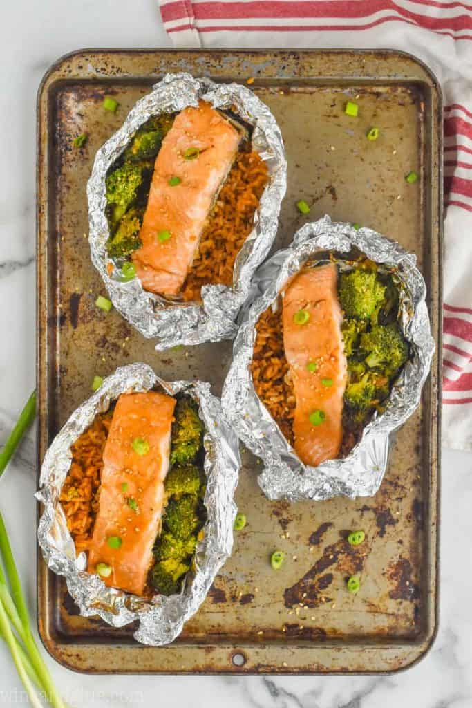 three baked teriyaki salmon foil packets on a baking sheet