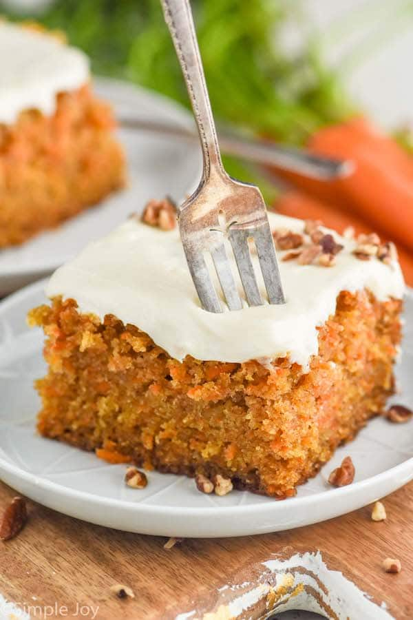 a fork sticking into a piece of carrot cake that is topped with cream cheese frosting