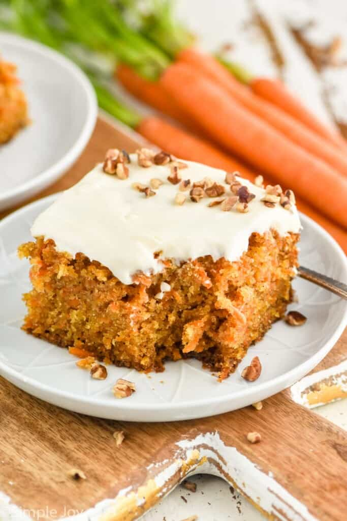 a piece of homemade carrot cake on a small plate with a bite missing