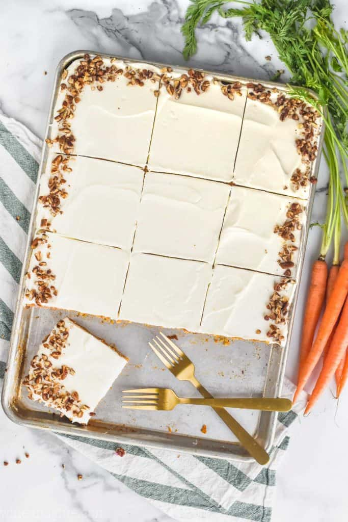 Overhead photo of the Carrot Cake Sheet Cake. The sheet cake is cut into 12 pieces with the bottom row of cake gone except one. The edges of the cake is sprinkled with chopped pecans