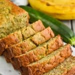 a side view of zucchini banana bread sliced on a marble cutting board with a zucchini and banana in the background