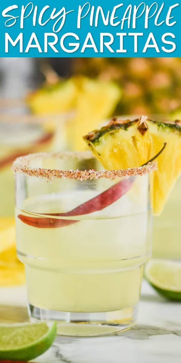 tumbler glass filled with spicy pineapple margarita and garnished with a chile pepper and a slice of pineapple