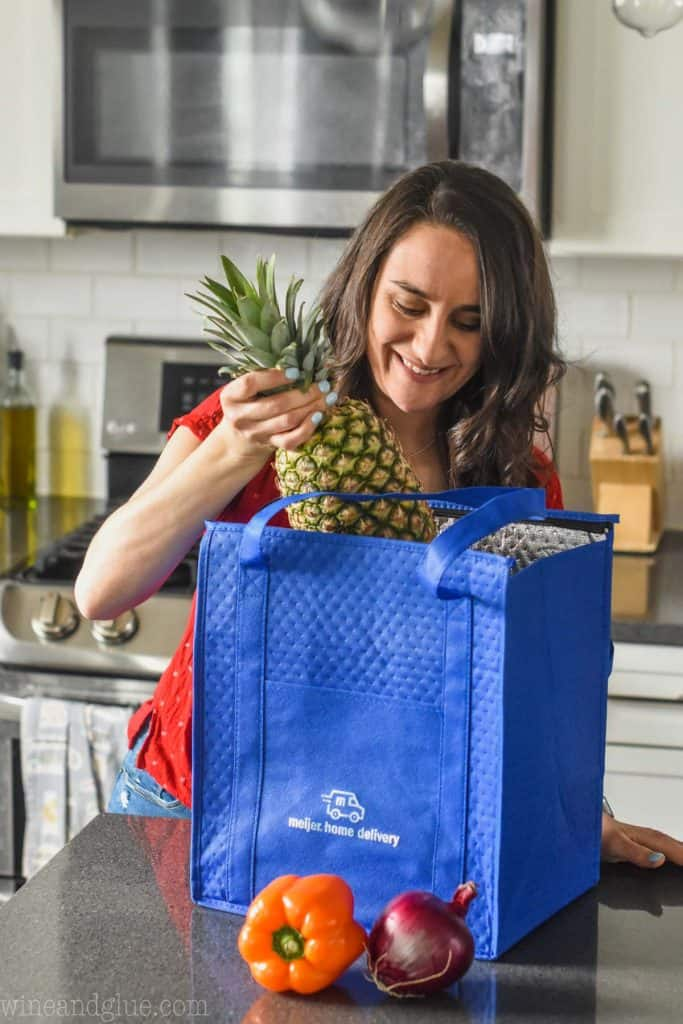 woman pulling a pineapple out of a meijer home delivery bag