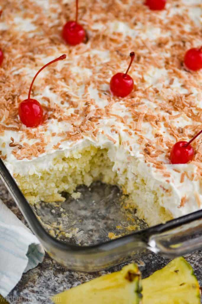 a sheet cake that has been made into a pina colada poke cake with a piece missing, frosted with toasted coconut on top and maraschino cherries