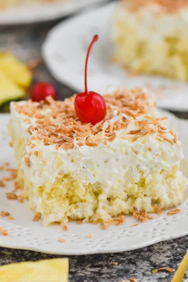 close up view of square piece of pina colada poke cake topped with frosting and toasted coconut on a white plate with a cherry on top
