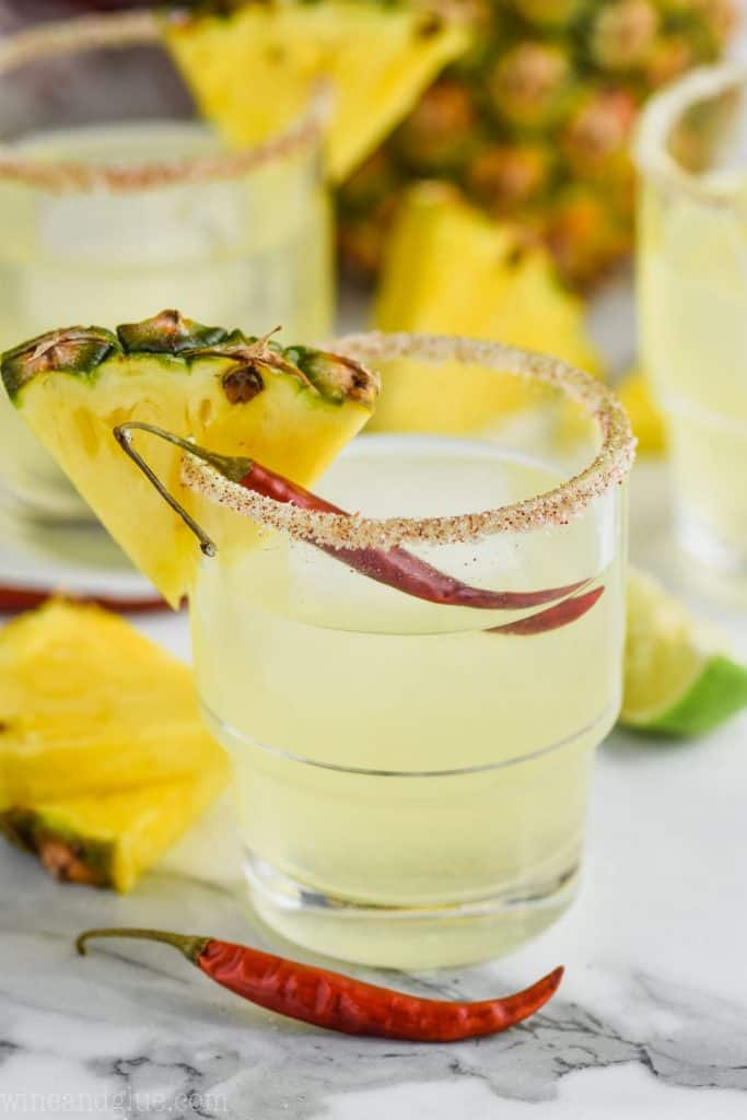 a glass of pineapple margarita garnished with a pineapple wedge and a chile pepper