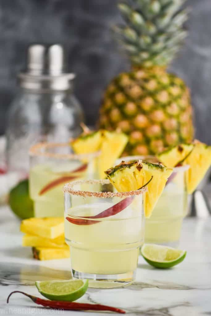 three glasses of pineapple margaritas garnished with pineapple wedges and red chile peppers