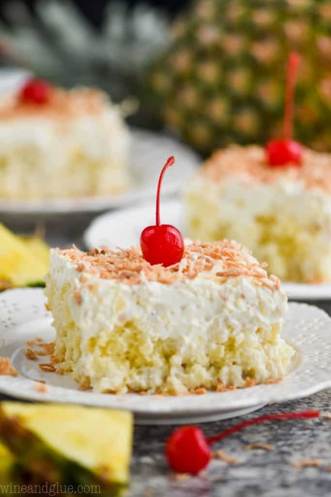 piece of pina colada poke cake topped with toasted coconut and cherry on a white plate