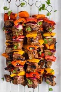 steak kabobs, skewered with metal skewers and flavored with fajita seasoning, on a white plate