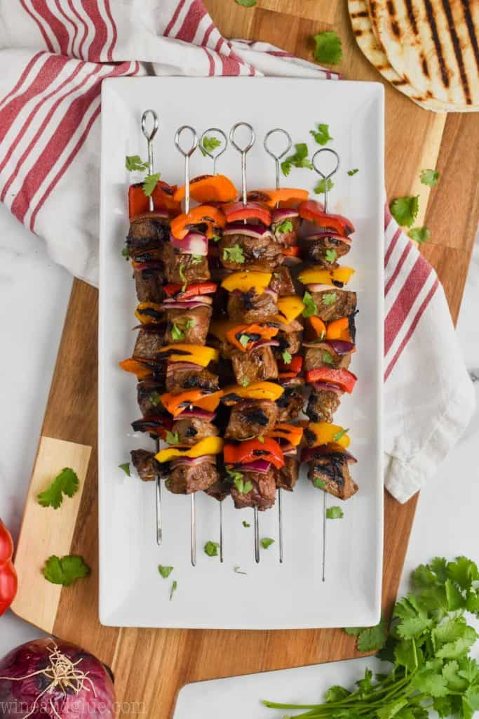 overhead view of beef kabobs on a white plate on a cutting board with grilled tortilla shells to make steak fajitas
