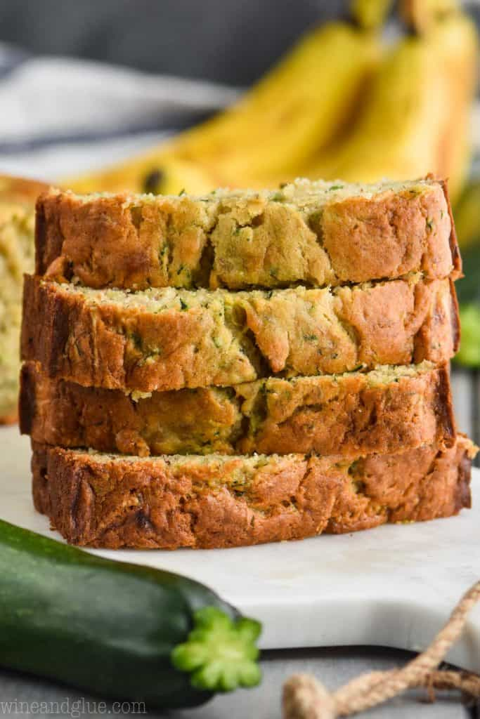 stack of slices of the best zucchini banana bread recipe on a marble cutting board with a zucchini in front and a banana bunch in the back