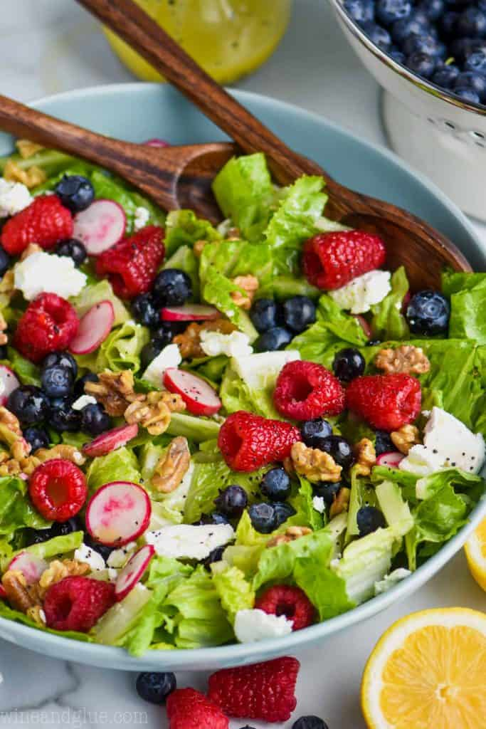 raspberries, blueberries, walnuts, goat cheese, radishes, and romain lettuce in a bowl for a great summer salad recipe