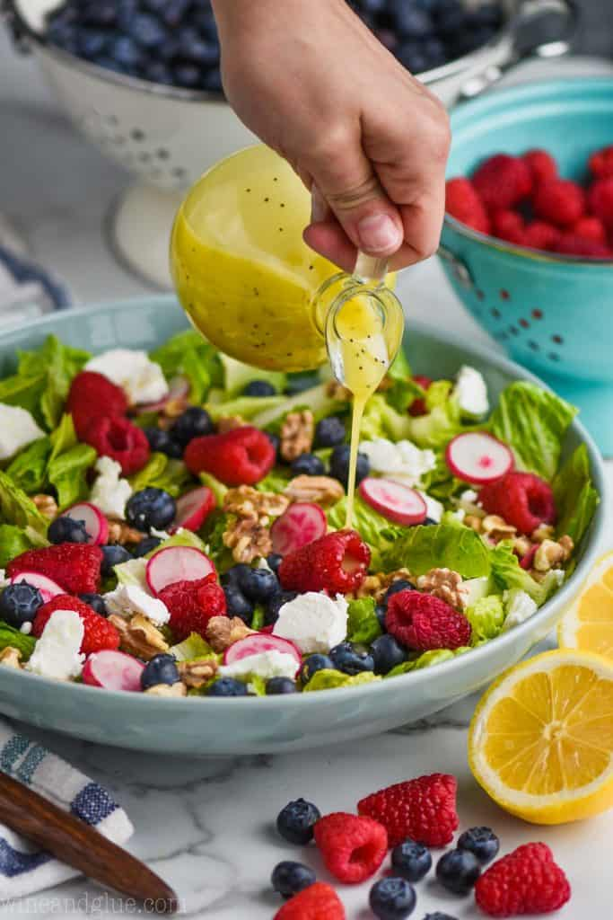 woman pouring lemon poppy seed dressing on a simple summer salad recipe