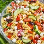 clear bowl with rotini noodles, vegetables, and feta cheese for a greek pasta salad recipe
