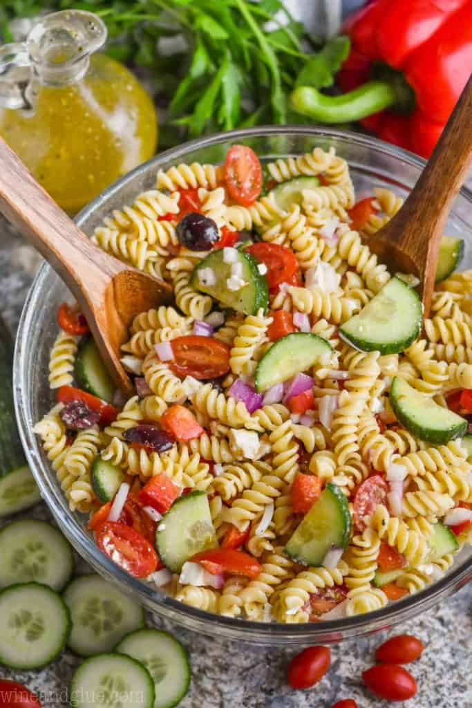overhead view of greek pasta salad in a bowl with wooden spoons