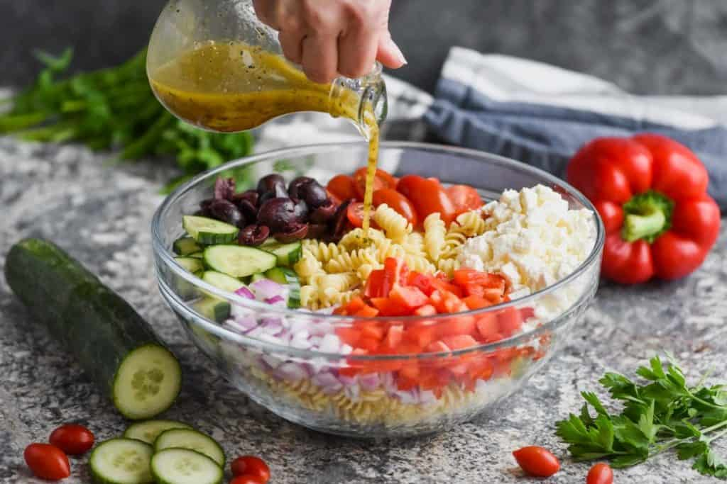 hand pouring greek salad dressing over a greek pasta salad in a clear bowl