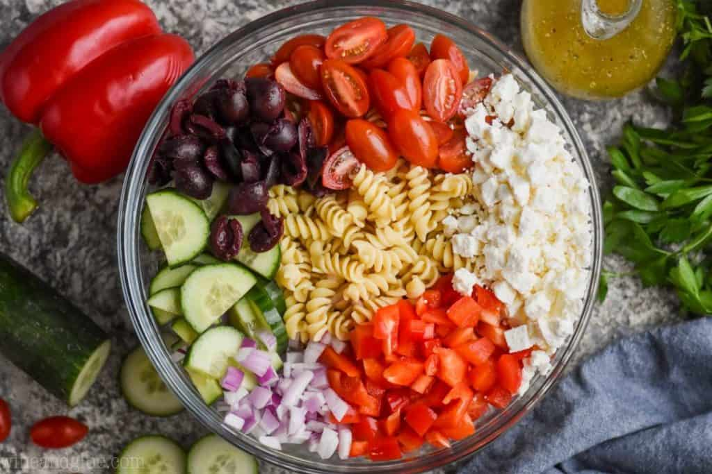 overhead view of greek pasta salad ingredients separated out in a bowl