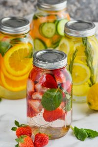 four mason jars filled with infused water