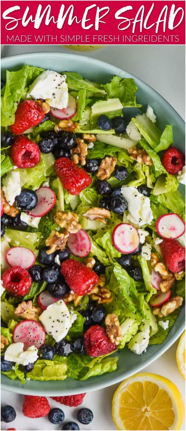 overhead view of a summer salad recipe with fresh raspberries, blueberries, radishes, romain lettuce, walnuts, and goat cheese all with a lemon poppyseed dressing in a big blue bowl