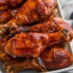 plate full of grilled chicken legs sitting on a striped napkin