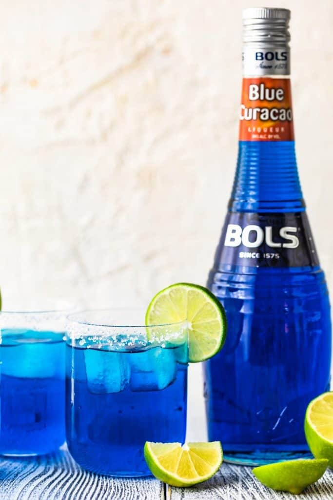 two glasses filled with blue margaritas, rimmed with salt, ganrished with a lime and with a bottle of bols blue curaçao next it