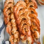 shrimp skewers, seasoned with cajun seasoning in a pile on a white rectangular dish
