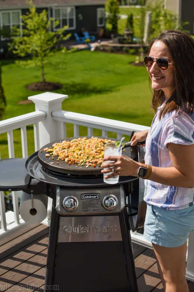 woman cooking shrimp stir fry on a cuisinart 360 griddle cooking center