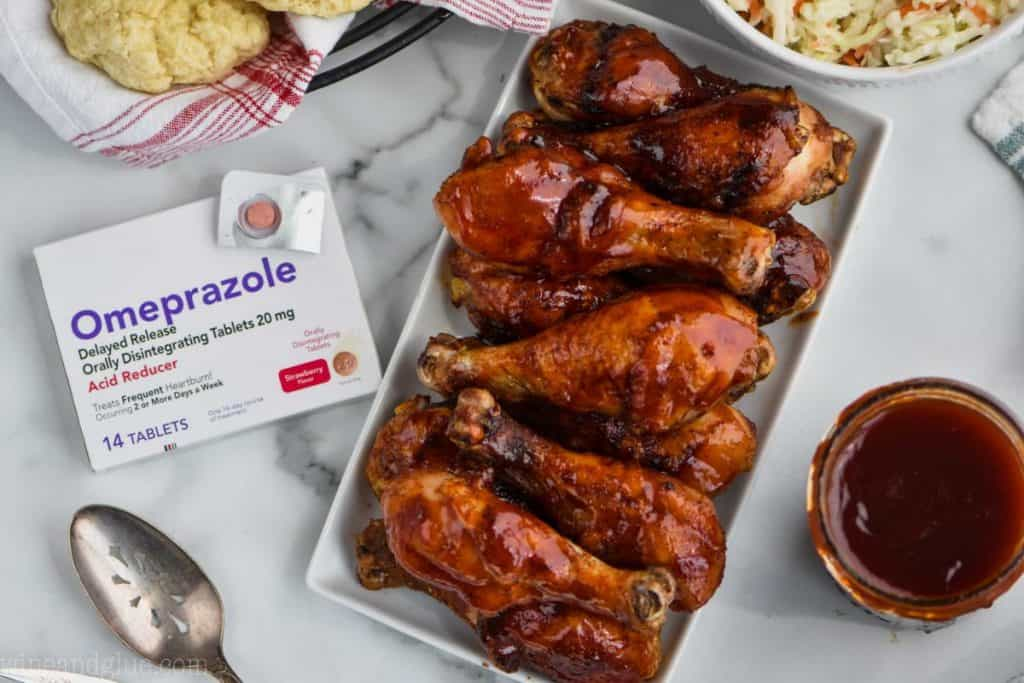 plate of bbq chicken drumsticks next to a box of heart burn medication