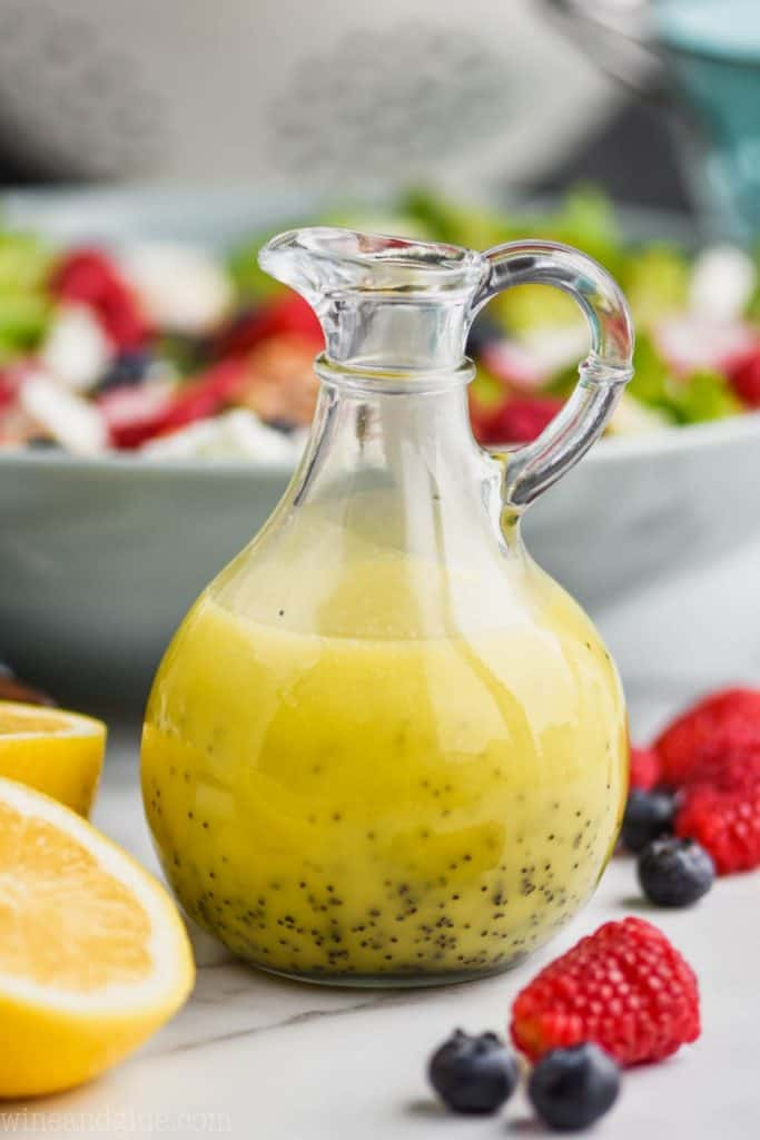 vinaigrette bottle surrounded by cut lemons, fresh raspberries and blueberries and filled with lemon poppy seed salad dressing