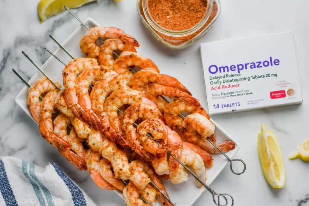 A plate full of Cajun Shrimp Skewer with lemon slices around the plate and a box of Omerprazole