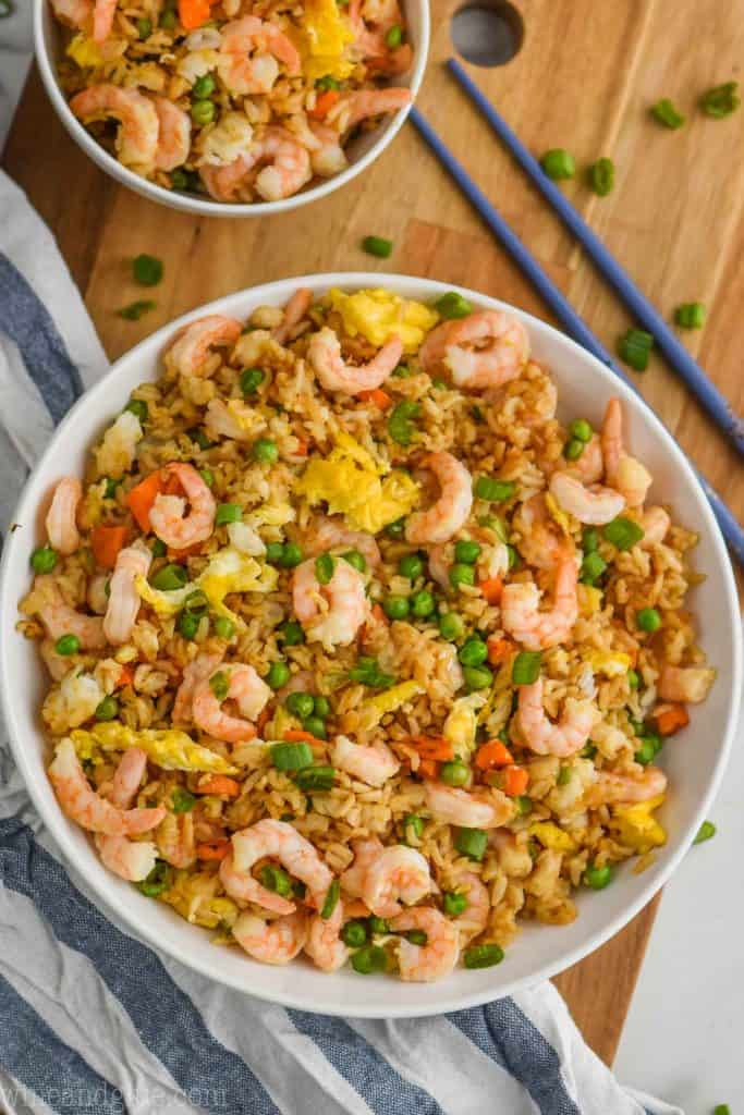 overhead view of bowl of shrimp fried rice recipe on a wood cutting board