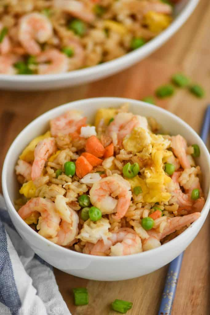 small white bowl filled with shrimp fried rice recipe on a cutting board with a cloth napkin next to it