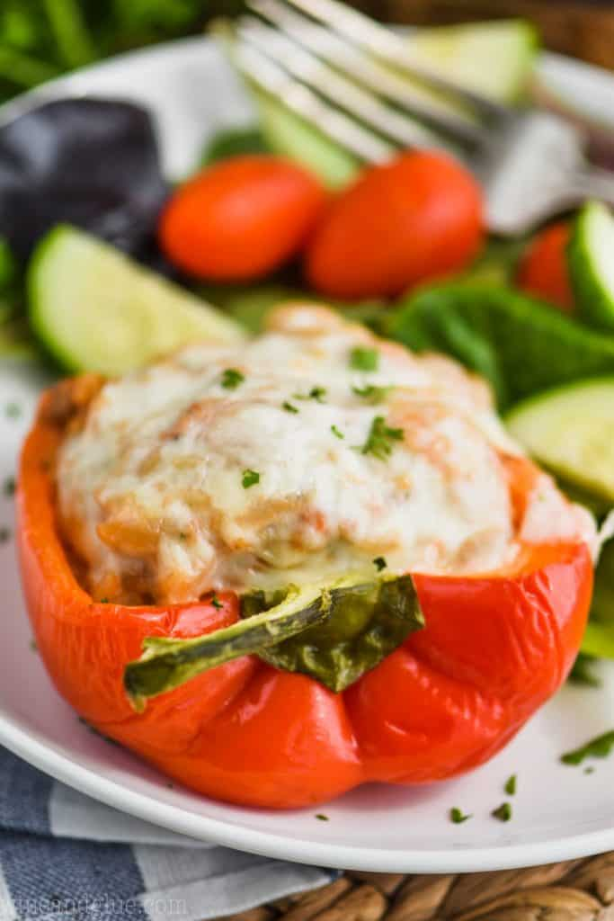 red bell pepper cut in half and stuffed with ground turkey, topped with provolone cheese and fresh parsley on a plate with salad