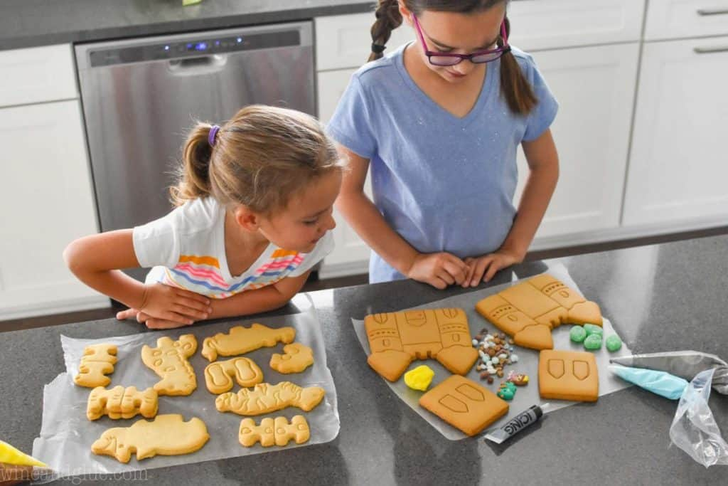 two little girls standing at a counter with supplies to decorate cookies