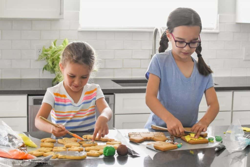 two little girls standing at a counter decorating cookies